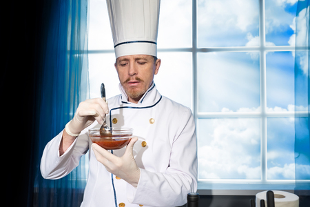 Cook in white uniform mixes the tomato sauce a spoon in a cup in the kitchen