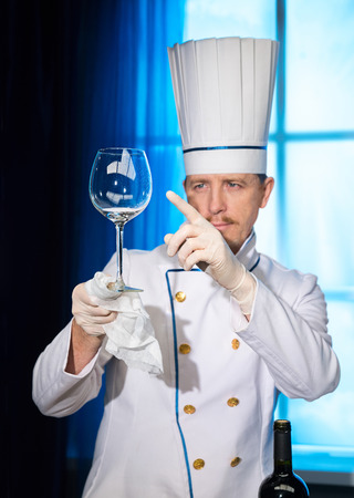 Chef in white uniform looks at a clean wine glass