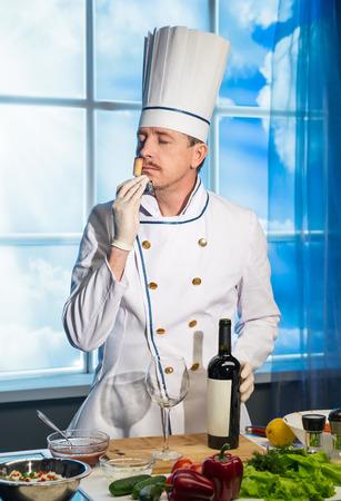 Chef in white uniform sniffs cork from wine Stock Photo