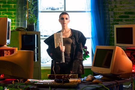 Female hacker with computer equipment and keyboard in hand