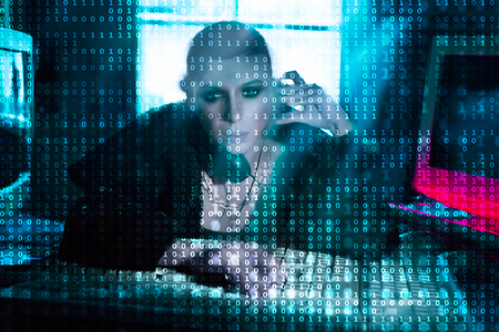 Female hacker at the computer over code background Imagens