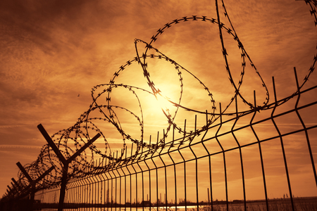 Prison barbed wire fence at sunset Фото со стока