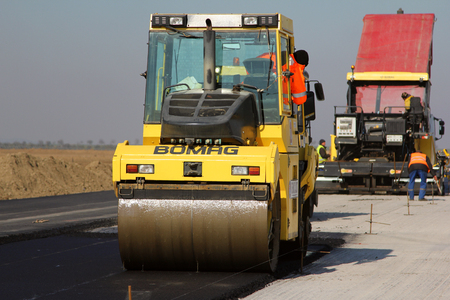 tracked: TULCEA, ROMANIA - NOVEMBER 08: Road roller leveling fresh asphalt pavement on a runway as part of the Danube Delta international airport expansion plan on November 08, 2015 in Tulcea, Romania.
