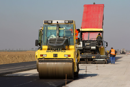 roller compactor: TULCEA, ROMANIA - NOVEMBER 08: Road roller leveling fresh asphalt pavement on a runway as part of the Danube Delta international airport expansion plan on November 08, 2015 in Tulcea, Romania.