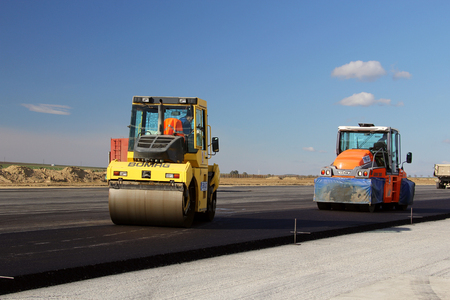 TULCEA, ROMANIA - NOVEMBER 08: Road rollers leveling fresh asphalt pavement on a runway as part of the Danube Delta international airport expansion plan on November 08, 2015 in Tulcea, Romania.