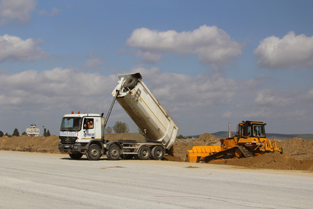 TULCEA, ROMANIA - SEPTEMBER 26: Dumper truck unloading soil on a runway construction site as part of the Danube Delta international airport expansion plan on September 26,2015 in Tulcea, Romania. Editorial