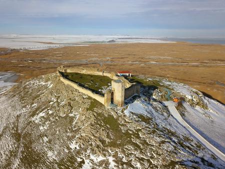 De ruïnes van middeleeuwse vesting Enisala in de winter (luchtmening), gelegen op een kalksteenheuvel in Dobrogea - Roemenië