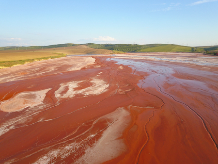 Aerial view of a reservoir full of red toxic sludge