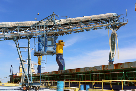 Conveyor belt loading ore into a capesize bulk carrier Stockfoto