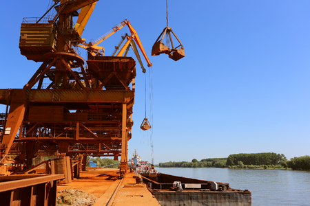 Industrial cargo port with operating cranes on the Danube river