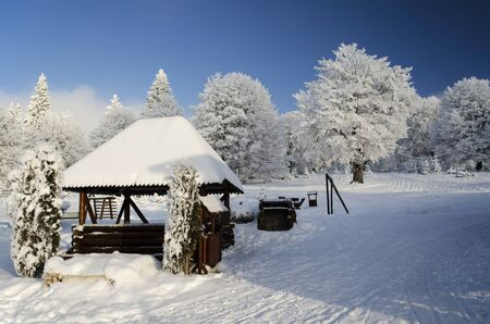 Winter landscape with little wooden house