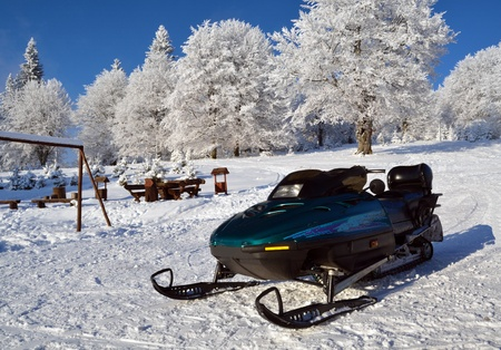 Ski jet (ski-doo) waiting for a rider in a beautiful winter landscape