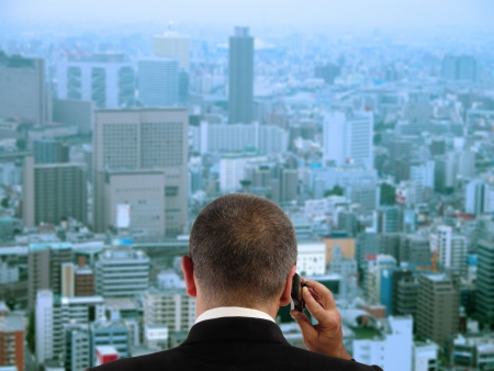 Businessman discussing to the mobile phone in his office while is looking through the window to the city.Focus on the businessman,the city aspect is blured. Stock Photo