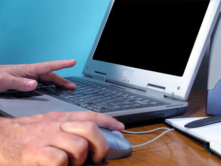 Hand working on a computer..focus on the distance hand.