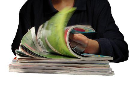 A girl riffling through magazines-over white background Stock Photo