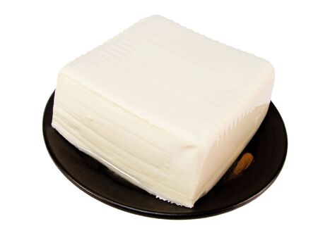 Tofu on a black wooden plate. This is raw tofu which can be cooked in different ways
