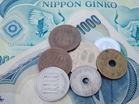 accounts payable: all the Japanese coins in use now and as background two 1000 yens bills Stock Photo