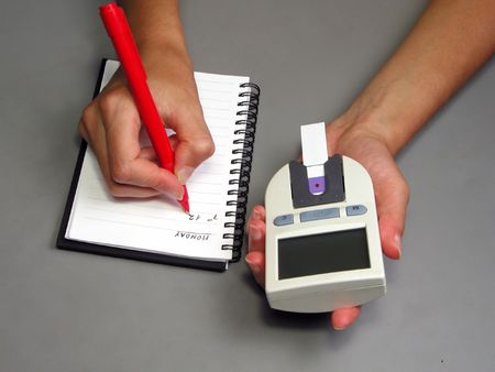 Two hands recording glycemia....usual attitude for a diabetic patient-educational self-monitoring image.