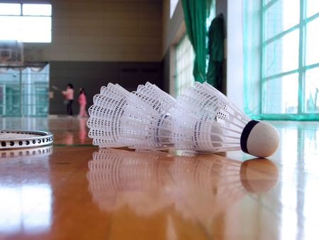 badminton racket: Perspective in a spots hall with shuttlecocks in the first plan. Stock Photo