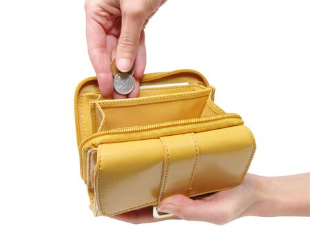 Woman hands putting coins in a wallet-isolated over white background with clipping path           Stock Photo
