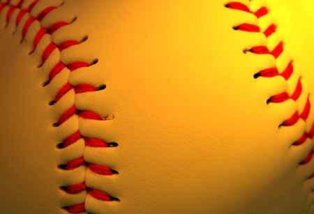 Extreme close up of a baseball in special lighting condition with selective focus on the left part.