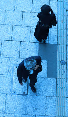 urbanscape: A man and a woman walking in different directions on a city street-upper blue view
