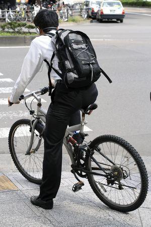 actief luisteren: Jonge man met een koptelefoon en rugzak fietsen in een stad. Stockfoto