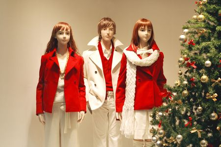 Winter holiday scene with young mannequins and Christmas tree in a shop window. photo