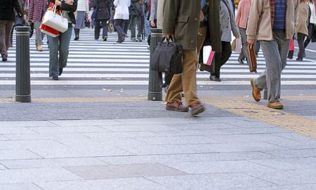 People crossing the street in a big city-very low perspective and soft focus. Stock Photo