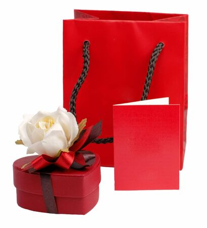 Valentine still life with heart shape chocolate box with rose on it,a red bag and a red card to put your message on it. photo