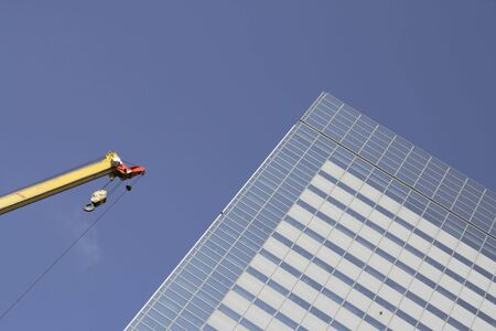 crane parts: Imagen de la parte superior de una gr�a y un rascacielos en una gran ciudad.