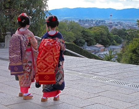 A very specific travel image for Kyoto,Japan:two geishas in front of Kyomizudera temple looking to the city with Kyoto Station tower visible in the distance. photo