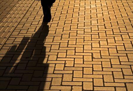 Sunset pavement reflections of a walking businessman photo