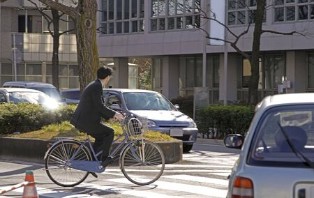 city bike: Businessman riding a bicycle in a crowded city traffic.