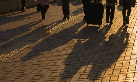 Image of travellers shadows on a pavement road in a dusk city. Stock Photo
