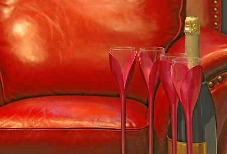 Still life with Champagne bottle, glasses and armchair. Stock Photo
