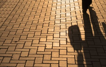 Sunset pavement reflections of a walking businessman with bag.