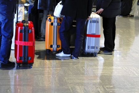 Image of some suitcases and persons legs in an airport. Stock Photo