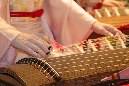 Detail of a geisha hand playing kato a traditional Japanese instrument. photo