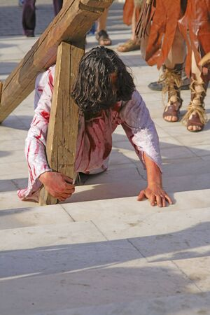 Jesus carrying the cross - aspect from a religious street show. Stock Photo