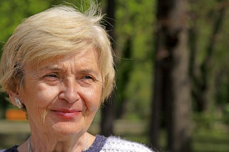 portraiture: Portrait of a smiling senior woman in a park.