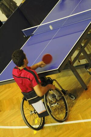 Image of a disabled man in wheelchair playing table tennis. Live image from an international tennis table competition for persons with disabilities.The use of flash lights was prohibited by organizers to not disturb the players.