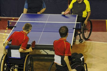 Image of a disabled persons in wheelchairs playing a double table tennis game. Live image from an international tennis table competition for persons with disabilities.The use of flash lights was prohibited by organizers to not disturb the players. photo