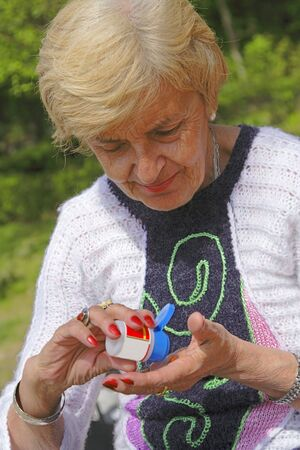 portraiture: Senior woman taking pills from a bottle in a park.