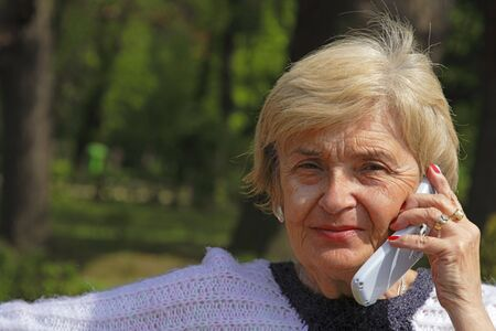 Image of an elderly woman using a mobile phone in a park. photo