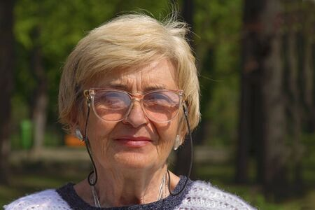 Outdoor portrait of a senior woman with glasses.