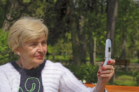 Senior woman using a mobile phone to take some pictures in a park. photo
