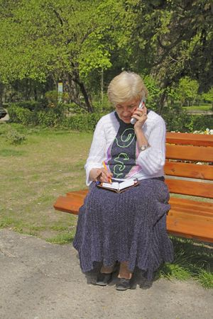 Woman calling by mobile phone and taking notice in a notebook in a park. Stock Photo - 990718