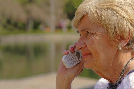 Profile of a senior woman using a mobile phone. photo