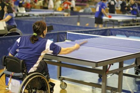 persona en silla de ruedas: Una mujer atleta con discapacidad jugando tenis de mesa en una competici�n oficial.